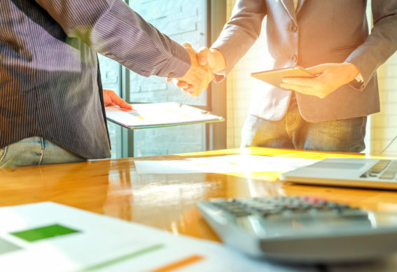 Businessmen shake hands when entering into business deal,In the hand are document files and smartphones.
