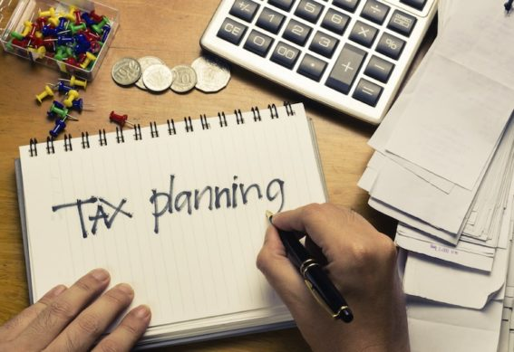 Hand writing Tax Planning word on the accountant desk