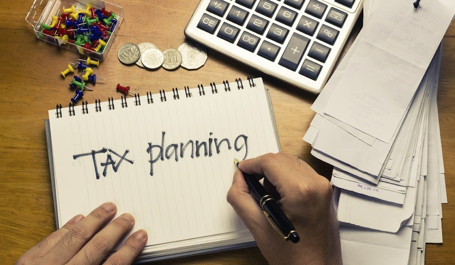 There are some coins, bills and pins and one calculator on the table. There is notebook with tax planning handwriting on it.